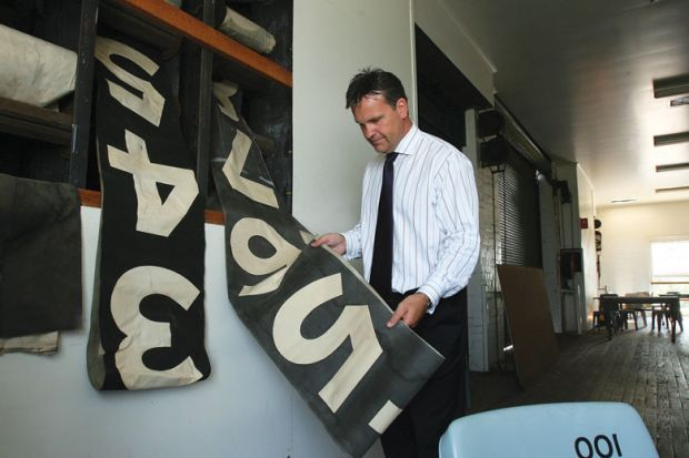 Man holding an old scoreboard as a metaphor for Staff counts are a numbers game