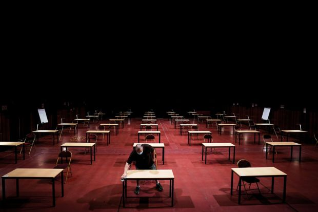 A man disinfects tables in an empty exam room as a metaphor for Is it time to rethink s tudent assessment?