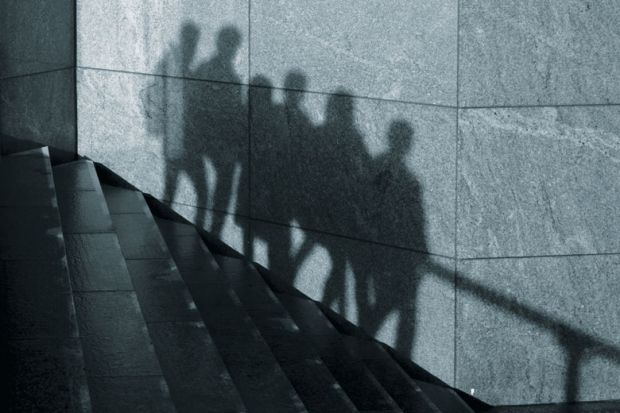 The shadows of anonymous people walking in one direction down stairs are seen on a wall in London as a metaphor for some students abusing privacy allowances