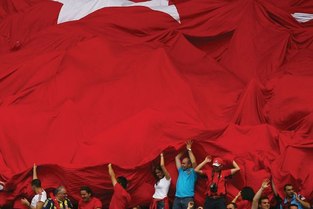 Fans of Turkey roll out the Turkish flag in support of their team