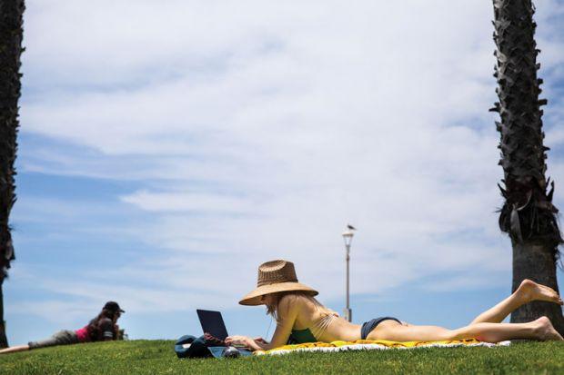 Person sunbathing in a bikini with her laptop