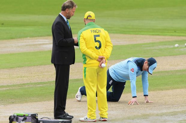 England captain Eoin Morgan inspects the pitch as match referee Chris Broad (l) chats with Australia captain Aaron Finch