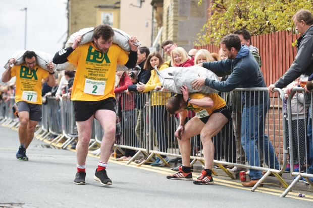 Competitors in a coal carrying race with large heavy sack on their back and one man from a crowd helping a sack on a competitors back as a metaphor  to Crowdfunding is increasingly a way for scholars and students at less prestigious universities to gain r