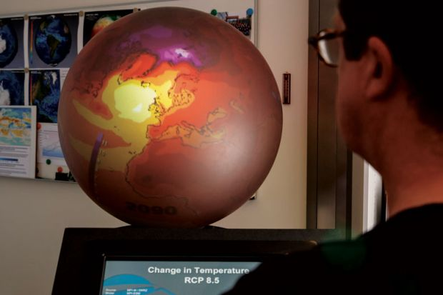 Person looking at screen next to supercomputer with red globe on top