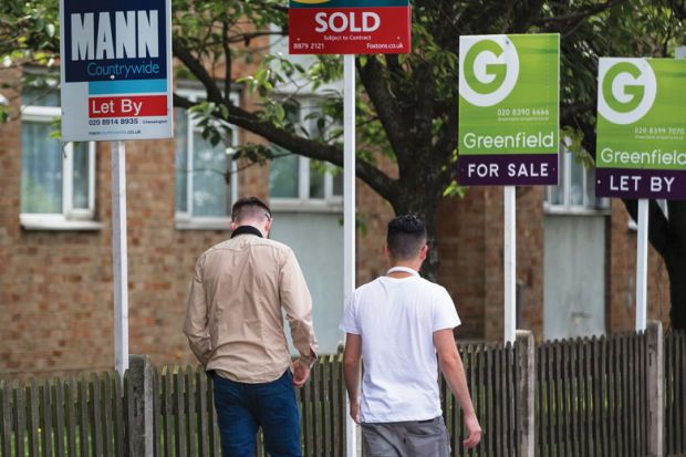 Pedestrians walk past estate agents' 'Let By', 'Sold', and 'For Sale' signs
