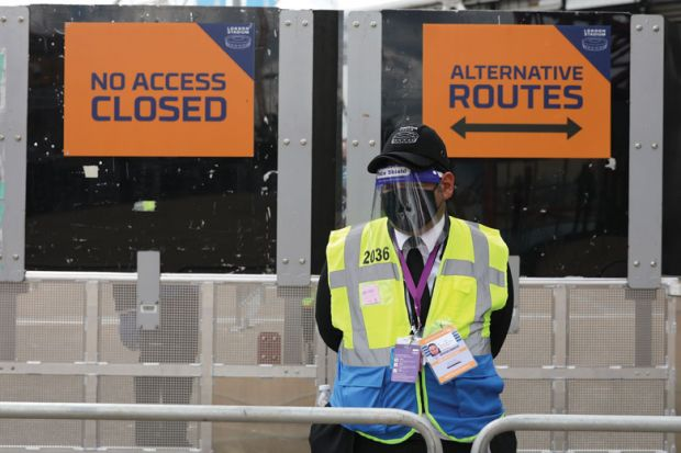 A steward in PPE including face mask and visor as a precaution against COVID-19 staffs a barrier at The London Stadium