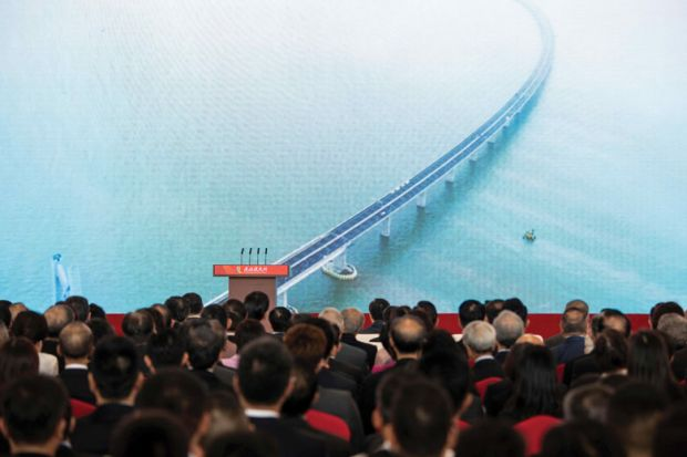 Guests watch a trailer on a giant screen during the opening ceremony of the Hong Kong-Zhuhai-Macau Bridge