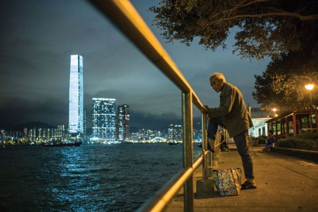 An elderly man rests his foot on a railing as he fishes in the waters of Victoria Harbour in Hong Kong