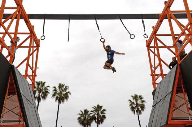 man swings across obstacle course
