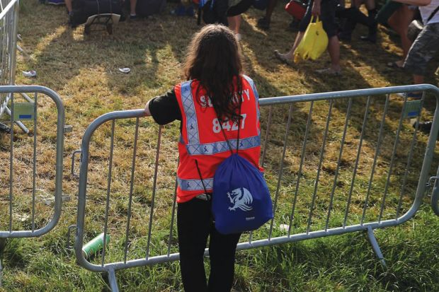 Security person holding gate at a festival