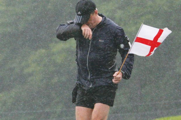 Man  soaking wet as he runs through Wiltshire holding a St Georges Flag.