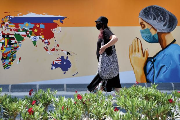 A woman wearing face mask walks past a mural depicting of a healthcare worker and a world map with flags on walls