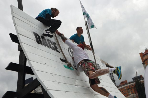 An athlete lends a helping hand to another contestant climbing up the warped wall