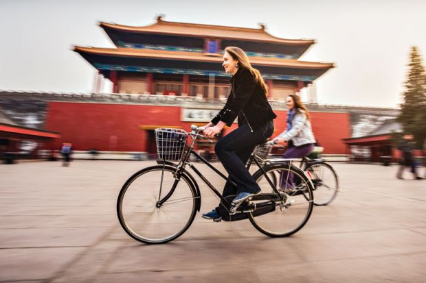 Friends riding retro bicycles along forbidden city