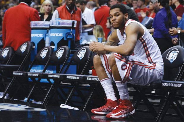 Amir Williams f the Ohio State Buckeyes sits on the bench by himself after losing  NCAA Men's Basketball Tournament
