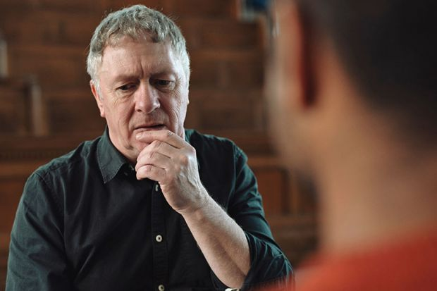 Man with grey hair and black shirt holding hand at mouth whilst thinking and talking to male
