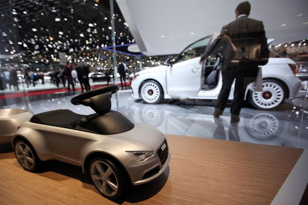 A toy car for Audi AG is seen on the company's stand with a man looking at white car in background