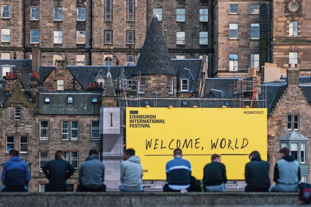 EDINBURGH, SCOTLAND - AUGUST 14: Citizen stand in front of the welcome sign of Edinburgh Festival Fringe on August 14, 2016 in Edinburgh, Scotland.
