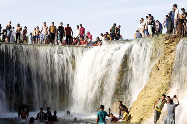 Egyptians enjoy a waterfall in Wadi El-Rayan