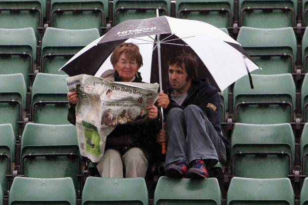 Woman and man read paper in rain