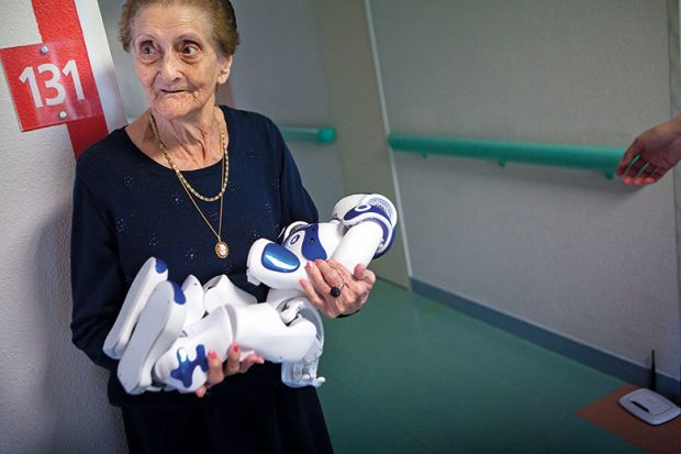 elderly woman holding robot