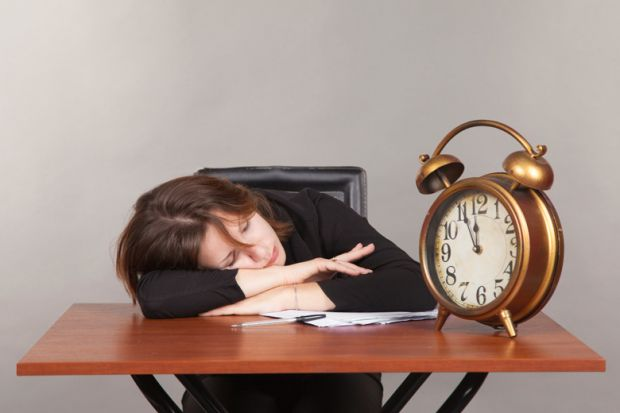 Woman asleep on desk with large alarm clock