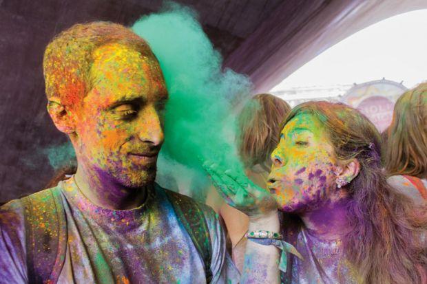 Woman blowing colour into male friend's face
