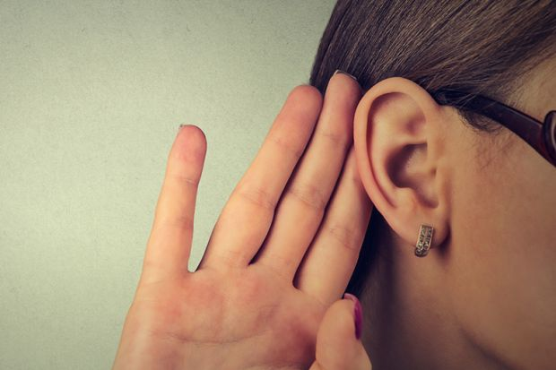 Woman cupping hand to ear to listen