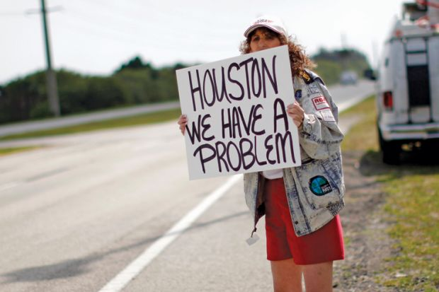 Woman holding 'Houston, we have a problem' sign