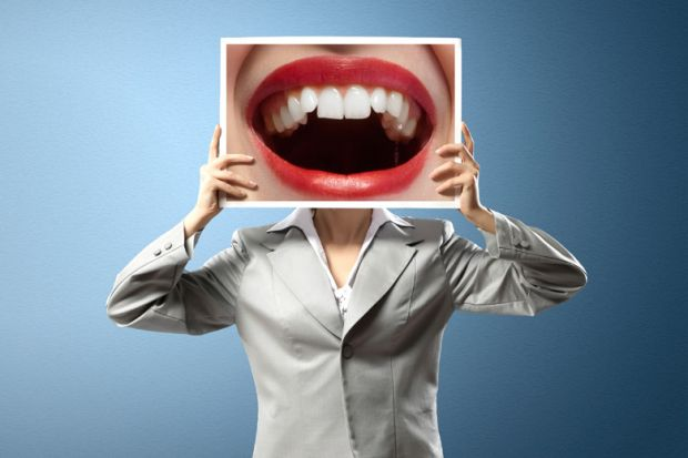 Woman holding photo of open mouth over face