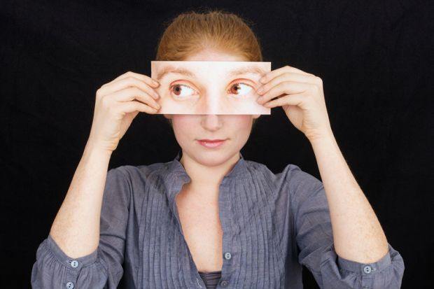 Woman holding print-out of eyes over face