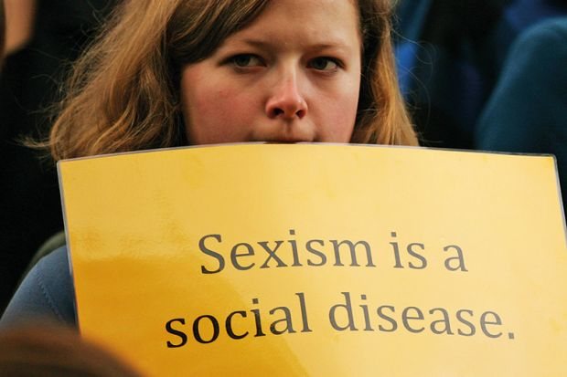 Woman holding sexism is a social disease sign