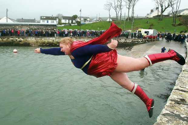 woman in superhero costume jumps into harbour