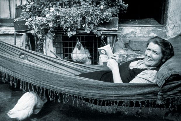 Woman lying in hammock reading book