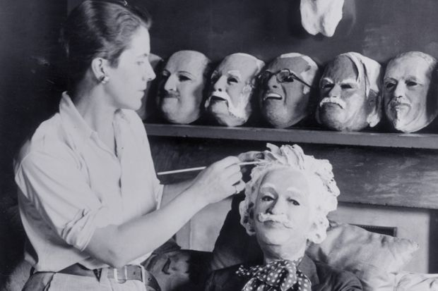 Woman making plaster puppet