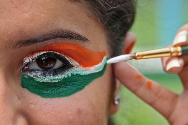 Woman painting eyes in colours of flag of India
