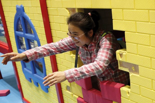 Woman playing with son at indoor playground, Beijing, China, 2015