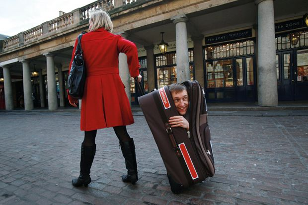 woman pulling along man hidden in suitcase