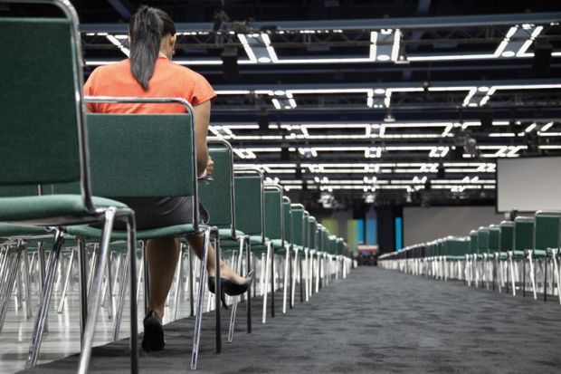 Woman sitting alone in empty conference centre