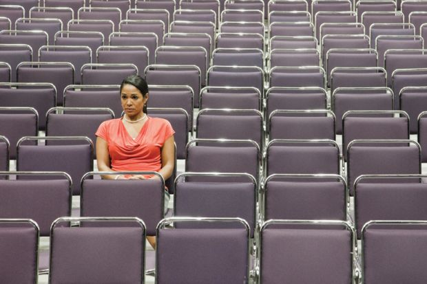 Woman sitting alone on empty lecture hall