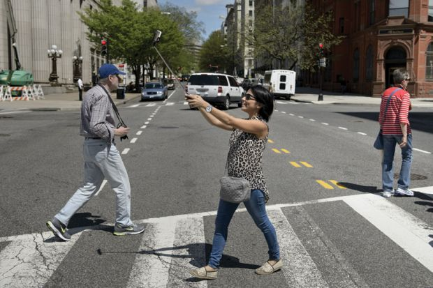 Woman using smartphone selfie stick while crossing road