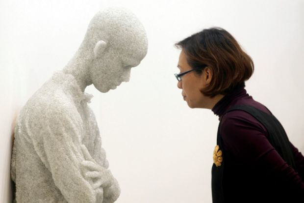 Woman viewing 'Figure with arms crossed' sculpture by Daniel Arsham, Singapore