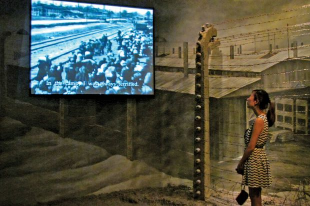 Woman viewing holocaust documentary on large-screen television
