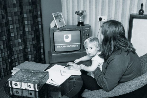 Woman watching The Open University on TV while holding child