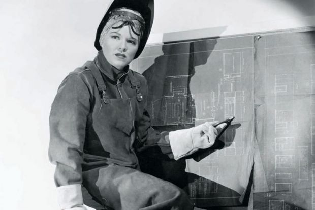 Woman wearing protective clothing pointing at blueprints
