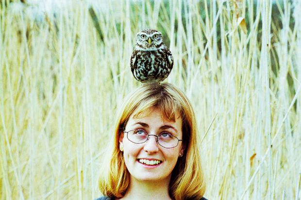 A woman with an owl balanced on her head