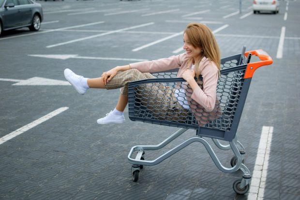 Woman sitting in shopping trolley