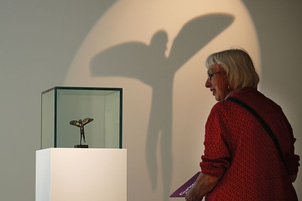 A woman looking at an item in a museum