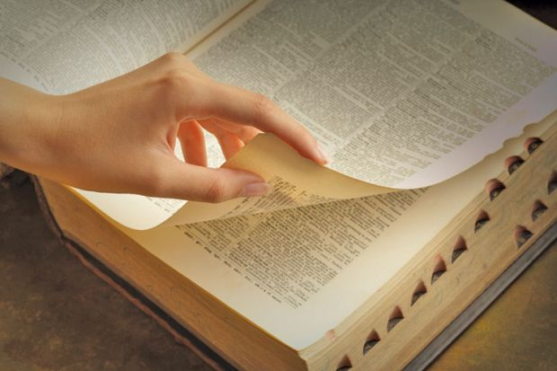 Woman's hand turning dictionary pages