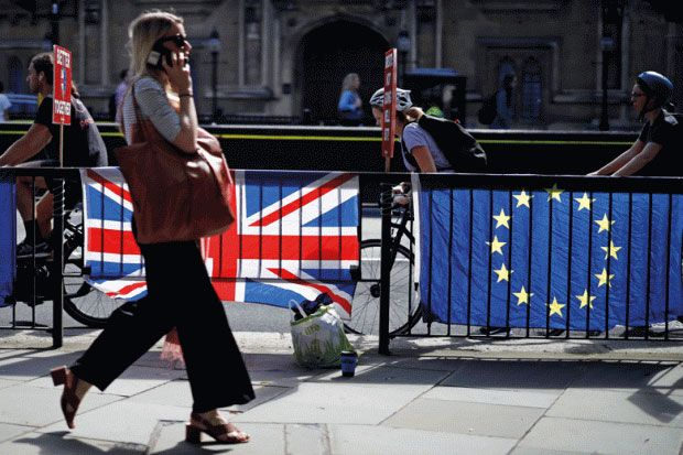 Woman walking past UK and EU flags